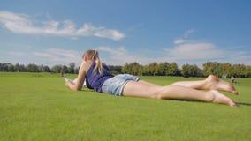 A zorra disparou da menina nova do estudante que encontra-se na grama no parque e que lê um livro filme