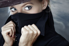 Zorro. Female spy in hat with face covered by the coat collar Stock Images