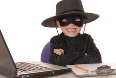 Zorro Help Desk 23. Child as costumed Zorro at laptop helpdesk Stock Images