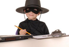 Zorro Help Desk 24. Child as costumed Zorro at laptop helpdesk Royalty Free Stock Photo