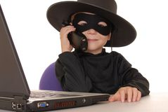 Zorro Help Desk 26. Child as costumed Zorro at laptop helpdesk Royalty Free Stock Images