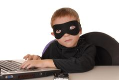 Zorro Help Desk 32. Child  costumed as Zorro at laptop helpdesk Royalty Free Stock Image