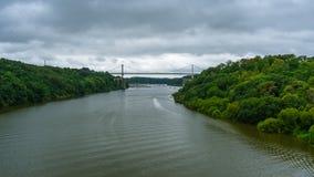 Zostający bridżowy w zielonym naturalnym lesie z dramatycznym chmurnym niebem, Motorboat żeglowanie na rzece zdjęcia stock