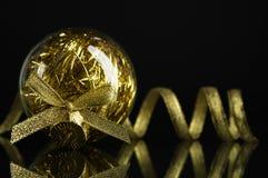 Złota xmas piłka, faborek na czarnym tle i Fotografia Royalty Free
