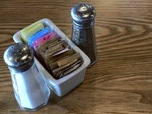 Zout en peperschudbekers met een container van suiker en suikersubstituut stock afbeeldingen