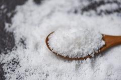 Zout in houten lepel en hoop van wit zout op dark royalty-vrije stock foto