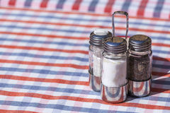 Zout, peper en tandenstoker die over een openluchtrestaurantlijst wordt geplaatst Stock Foto's