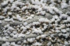 Zoute kristallen op grijs zand Royalty-vrije Stock Foto's