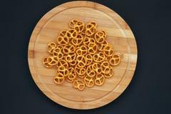 Zoute pretzels op ronde houten raad op donkere achtergrond, royalty-vrije stock foto's