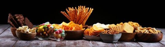 Zoute snacks Pretzels, spaanders, crackers in houten kommen op lijst stock afbeeldingen