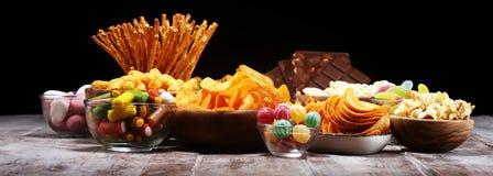 Zoute snacks Pretzels, spaanders, crackers in houten kommen op lijst stock foto's