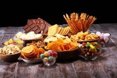 Zoute snacks Pretzels, spaanders, crackers in houten kommen op lijst stock fotografie