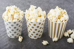 Zoute verse knapperige eigengemaakte popcorn in zilveren document kop op de manier lichte achtergrond van witte bakstenen muur in Royalty-vrije Stock Afbeelding