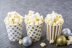 Zoute verse knapperige eigengemaakte popcorn in zilveren document kop op de manier lichte achtergrond van witte bakstenen muur in Royalty-vrije Stock Afbeeldingen