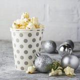 Zoute verse knapperige eigengemaakte popcorn in zilveren document kop op de manier lichte achtergrond van witte bakstenen muur in Royalty-vrije Stock Foto