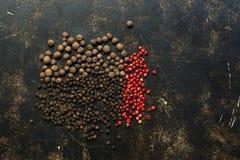 Zróżnicowani peppercorns na ciemnym nieociosanym tle Odgórny widok, kopii przestrzeń obraz stock