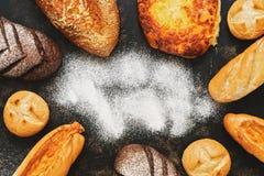 Zróżnicowany chleb, babeczki, bochenek na ciemnym tle z mąką Odgórny widok, kopii przestrzeń Set różnorodny domowej roboty chleb fotografia royalty free