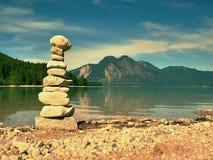 Zrównoważony kamienny pyramide na brzeg błękitne wody halny jezioro Zdjęcia Royalty Free