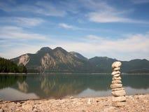 Zrównoważony kamienny pyramide na brzeg błękitne wody halny jezioro Zdjęcie Royalty Free