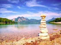 Zrównoważony kamienny pyramide na brzeg błękitne wody halny jezioro Zdjęcie Stock