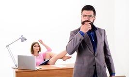 Zręcznie i fachowy Biznesowa i fachowa kobieta pracuje przy miejsce pracy z brodatym mężczyzną w przedpolu Seksowny obraz royalty free