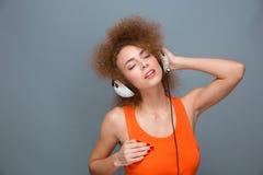 Zrelaksowana beztroska kędzierzawa kobieta słucha muzyka w słuchawkach Fotografia Royalty Free