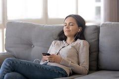 Zrelaksowana dziewczyna jest ubranym słuchawki słucha muzyka bawić się przez smartphone obrazy stock
