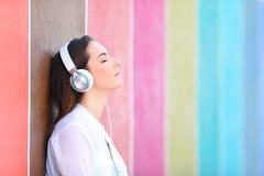 Zrelaksowana dziewczyna słucha muzyka w kolorowej ulicie zdjęcie stock