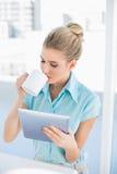 Zrelaksowana elegancka kobieta używa pastylkę podczas gdy pijący kawę obrazy royalty free