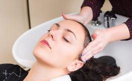 Zrelaksowana kobieta Ma włosy Myjącego w salonie Zdjęcia Royalty Free