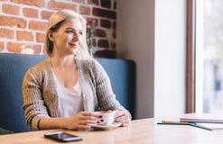 Zrelaksowana kobieta pije kawę w kawiarni zdjęcie royalty free