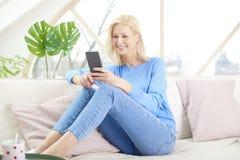 Zrelaksowana kobieta relaksuje w domu i używa przydatny zdjęcia stock