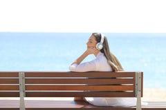 Zrelaksowana kobieta słucha muzyka na ławce obrazy royalty free