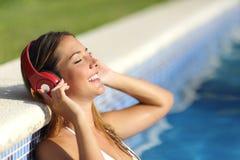 Zrelaksowana kobieta słucha muzyka z hełmofonami Zdjęcia Royalty Free