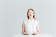 Zrelaksowana kobieta siedzi przy stołem z zamkniętymi oczami Obrazy Royalty Free