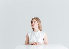 Zrelaksowana kobieta siedzi przy stołem z zamkniętymi oczami Fotografia Royalty Free