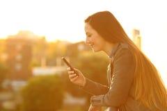 Zrelaksowana kobieta sprawdza mądrze telefon w balkonie zdjęcie stock