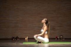 Zrelaksowana kobieta stawia jej głowę w górę podczas gdy medytujący z zamkniętymi oczami zdjęcie stock