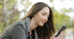 Zrelaksowana kobieta używa mądrze telefon w parku