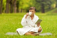 Zrelaksowana kobieta używa pastylkę, jest usytuowanym na trawie w bathrob zdjęcia royalty free