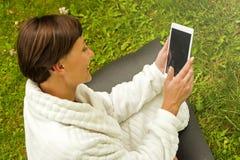 Zrelaksowana kobieta używa pastylkę, jest usytuowanym na zielonej trawie obrazy stock
