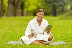 Zrelaksowana kobieta używa pastylkę, jest usytuowanym na zielonej trawie w bathrob Obraz Stock