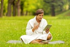 Zrelaksowana kobieta używa pastylkę, jest usytuowanym na zielonej trawie w bathrob obrazy stock
