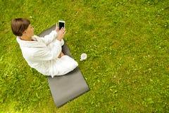 Zrelaksowana kobieta używa pastylkę, jest usytuowanym na zielonej trawie w bathrob fotografia royalty free