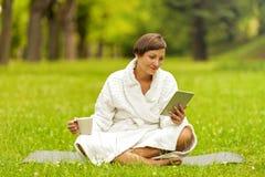 Zrelaksowana kobieta używa pastylkę, jest usytuowanym na zielonej trawie w bathrob zdjęcie stock