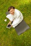 Zrelaksowana kobieta używa pastylkę, jest usytuowanym na zielonej trawie w bathrob zdjęcia stock
