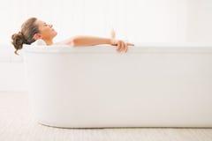 Zrelaksowana młoda kobieta kłaść w wannie Zdjęcia Stock