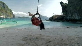 Zrelaksowana młoda kobieta w czerwieni sukni huśta się na arkany huśtawce na spokojnej piaskowatej plaży na słonecznym dniu samoc zbiory