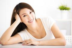 Zrelaksowana młoda uśmiechnięta kobieta w żywym pokoju zdjęcia stock