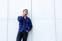 Zrelaksowana młody człowiek pozycja przeciw biel ścianie w błękitnej koszula Fotografia Royalty Free